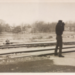 Man taking photographs near the railroad tracks during the flood of 1959.