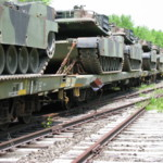 Army tanks being delivered from the Ravenna Arsenal to Aberdeen Proving Grounds in Maryland.  The Conductor, Michael Melcusney is checking is checking to make sure the tanks are secured to the flatbed cars.