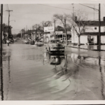 Cars ford the floodwaters on South Main Street during the flood of 1959.