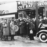 Crowd at bus stop in front of Weinberger Drug Store, 109 W Market Street.